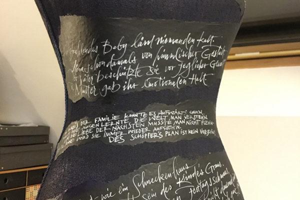 Beschriftung einer Kleiderpuppe mit Gedicht vom Auftraggeber